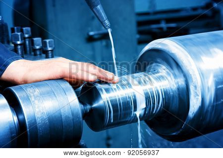 Worker measuring on industrial turning machine at work. Industry, precision.