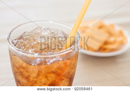 A Glass Of Cola With Snack On White Plate