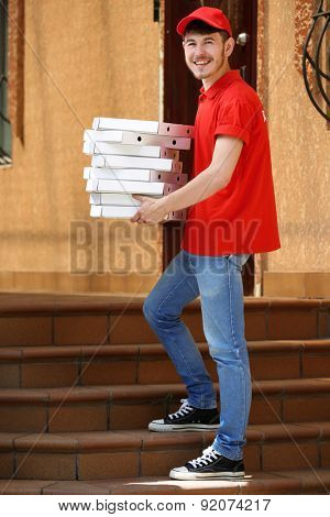 Delivery boy with cardboard pizza box near house of customer, outdoors