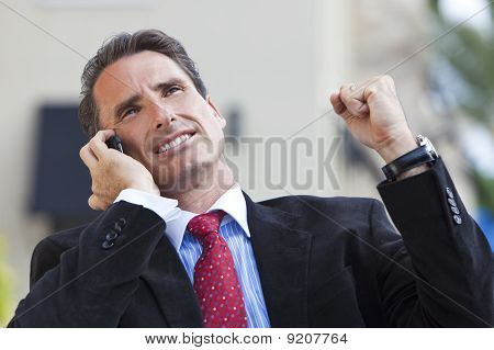 Male Executive Businessman Celebrating Success On Cell Phone