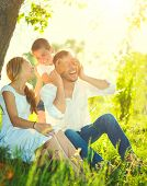 Happy joyful young family father, mother and little son having fun outdoors, playing together in summer park. Mom, Dad and kid laughing and hugging, enjoying nature outside. Sunny day, good mood poster