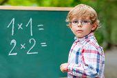 Adorable preschool kid boy with glasses at blackboard practicing mathematics outdoor. school or nursery. Back to school concept poster