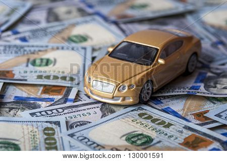 Golden Toy automobile on the background of one hundred dollar bills