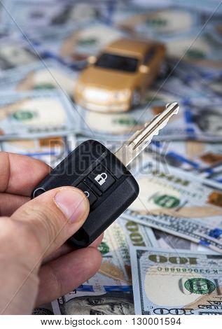 Male hand with car key on the background of toy car on dollar bills. Selective focus