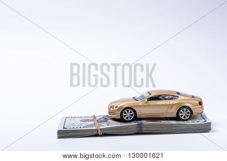 Golden toy car on dollars stack with rubberband on white background.