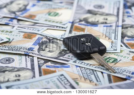 Car key and heap of one hundred dollar bills. Selective focus.