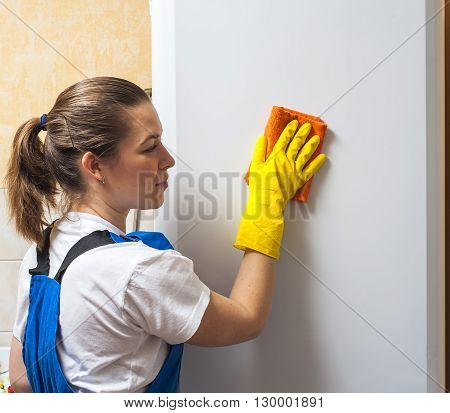 Female janitor cleaning refrigerator door with rag