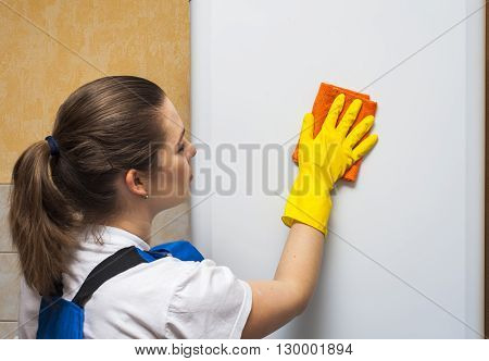 Female janitor cleaning refrigerator door with rag.