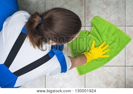 Female janitor in work wear cleaning floors