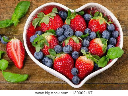Fresh Berries In Heart Shaped Bowl. Healthy Food Concept.