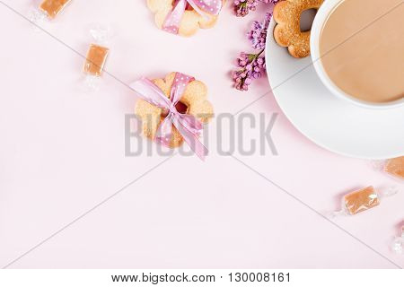 Cup of coffee with cookies candies and lilac flowers