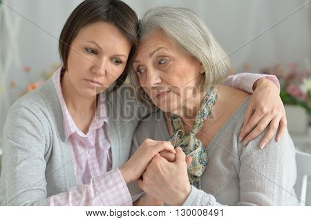 miserable senior mother and adult daughter together