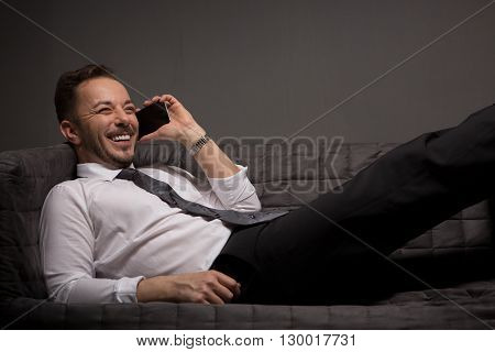 Happy businessman talking over mobile phone whie lying on comfortable sofa after hard-working day. Studio shot.