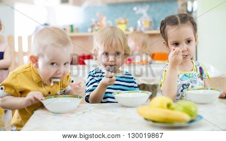 children eating from plates in day care centre