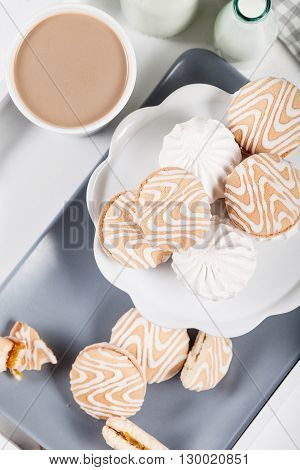 Cookies on white and gray plate with cups of coffee and bottles of milk on white shutters background top view