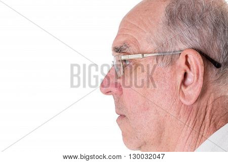 Face of old man in golden glasses closeup. Side view. Isolated on a white background.