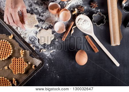 Waffles ingredients like eggs flour cinnamon anise rolling pin paper on blackboard from the top
