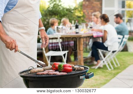 Close up hands of a senior man barbequing in the garden with family in background. Grandfather cooking on grill. Man cooking hamburgers, sausages and peppers with barbeque.