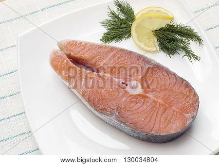 Raw salmon steak with lemon and dill on a white plate