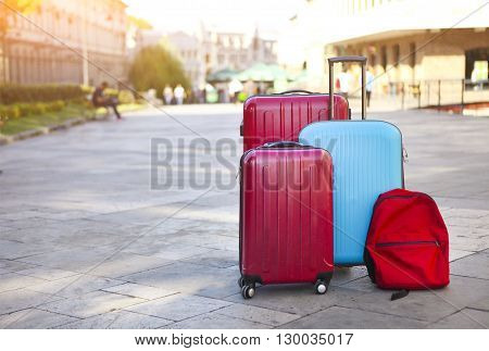 Luggage consisting of three large suitcases and travel backpack on the street. Holiday and travel concept poster