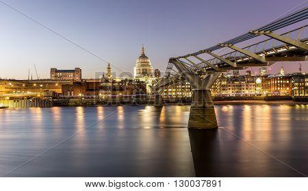 Millennium Bridge and St. Pauls church in London at sunset