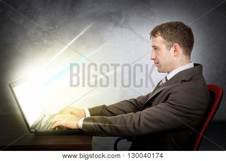 Cropped shot view of young businessman in front of table with laptop. E-business concept. Man in suit typing text on laptop. Monitor of laptop shine rays of light