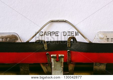 closeup of an old typewriter and the text carpe diem typewritten with it in a foil