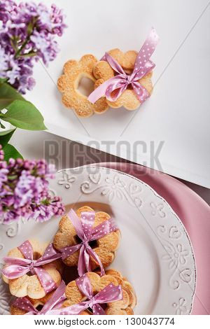 Cookies with pink ribbons on a white plate with lilac flowers