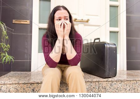 portrait of woman crying at the doorway with a suitcase as concept of divorced woman
