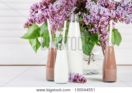 Bottle of milk and small bottles of chocolate milkshake with lilac flowers in a vase on white shutter background