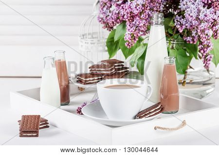 Cup of coffee and few bottles of milk and chocolate miklshakes on a white tray with lilac flowers on white shutters background