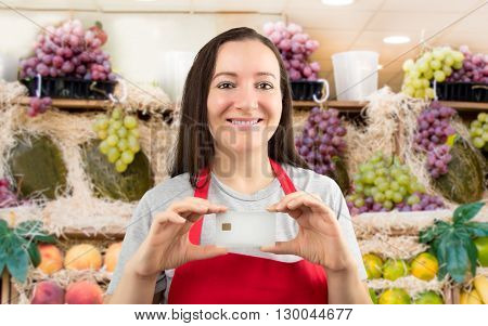 smiling shopwoman showing credit cart with copy space at the fruit shop