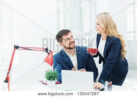 The smiling male and female office workers with laptop