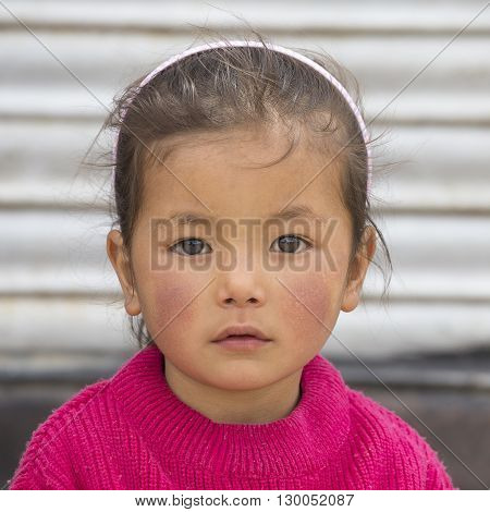 LEH INDIA - JUNE 24 2015: Unidentified poor Indian beggar girl on street in Ladakh. Children of the early ages are often brought to the begging profession.