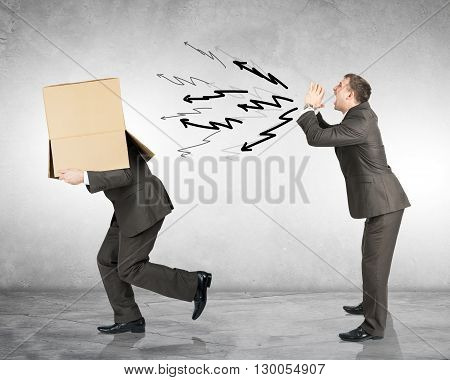 Business boss shouting to employee with box on his head