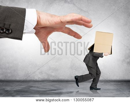 Business boss hand catching employee with box on his head