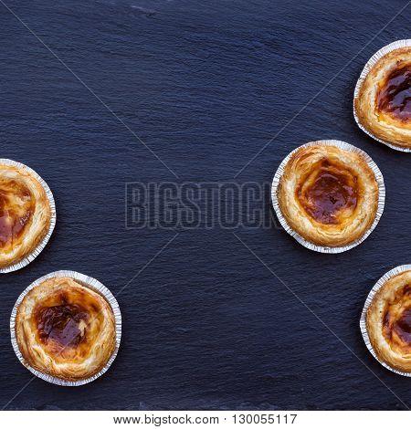 Egg tart on a grunge background, traditional portuguese dessert, pasteis de nata. Selective focus, flat lay
