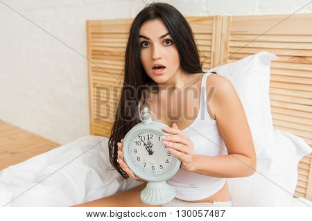 Young woman with alarmclock on the bed