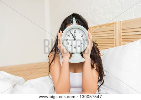 Young woman hiding with alarmclock on the bed