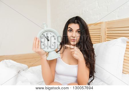 Smiling woman with alarmclock on the bed on pointing on it