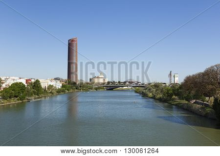 Seville, Spain - May 1, 2016: View of Guadalquivir river with Sevilla Tower, Torre Triana, Schindler Tower and Puente del Cachorro at Puerto Triana quarter.
