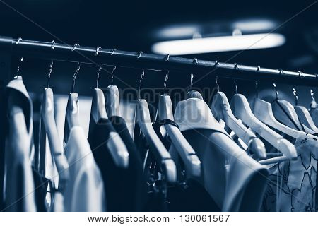 Clothes hangers in fashion store. Clothes business concept blue. Selective focused