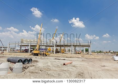 Mobile crane is loading cargo. View on construction site with machinery people at work.