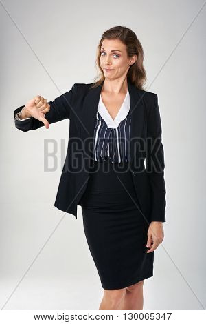 Businesswoman giving a thumbs down, showing her disapproval  isolated in studio