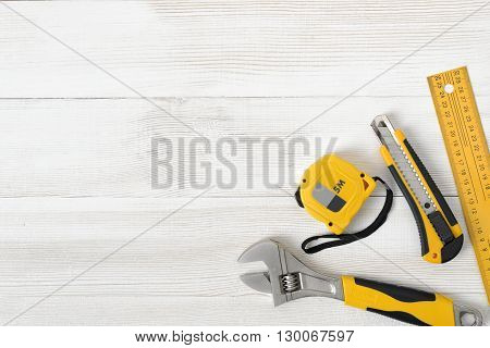 Construction tools including centimeter ruler, wrench and cutter placed in the right down corner on wooden surface with open space. Top view composition. Measurement. Fixing and cropping. Hand tool. Tools for carpentry work. Type of fastener. Mend and rep poster
