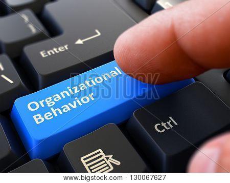 Finger Presses Blue Button  Organizational Behavior on Black Keyboard Background. Closeup View. Selective Focus. 3D Render.