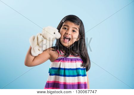 cute little indian girl playing with white soft toy puppet or puppet soft toy or puppet teddy bear isolated over blue background, asian small girl playing with puppet soft toy