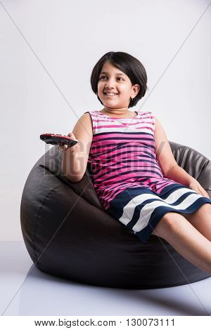 little indian girl watching tv or television and switching channels with remote control, cute asian girl with TV remote control in hand, white background