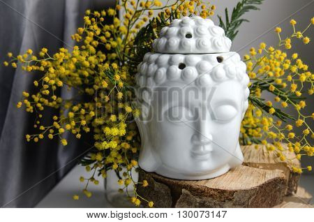 spiritual ritual meditation face of Buddha on wood, home decor, mimosa yellow spring flowers on the white wall background