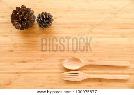 Wooden spoon fork and pine cones on wood texture of dining table from top view - use for background in food kitchen and christmas decoration concept